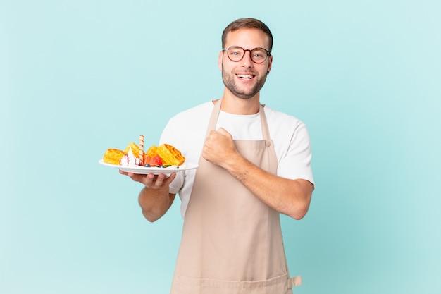 Jonge knappe blonde man voelt zich gelukkig en staat voor een uitdaging of feest. wafels koken concept