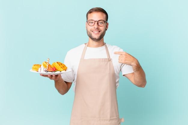 Jonge knappe blonde man voelt zich gelukkig en wijst naar zichzelf met een opgewonden wafels koken concept