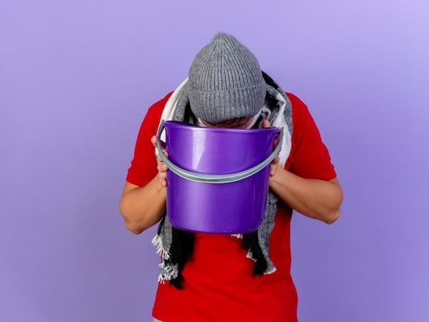 Jonge knappe blonde zieke man met muts en sjaal met plastic emmer erin te braken geïsoleerd op paarse muur
