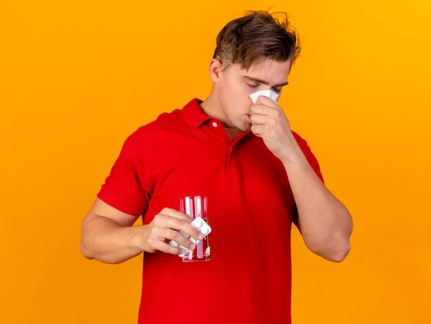 Jonge knappe blonde zieke man met pakje medische tabletten en glas water neus afvegen met servet met gesloten ogen geïsoleerd op een oranje achtergrond