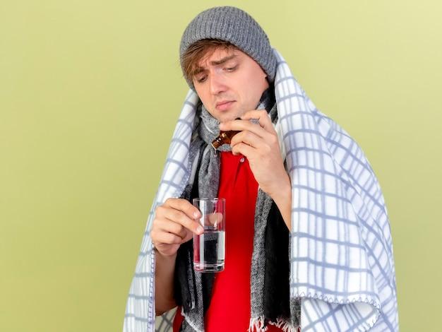 Jonge knappe blonde zieke man met winter hoed en sjaal verpakt in geruite medicament in glas gieten in glas water geïsoleerd op olijfgroene achtergrond met kopie ruimte