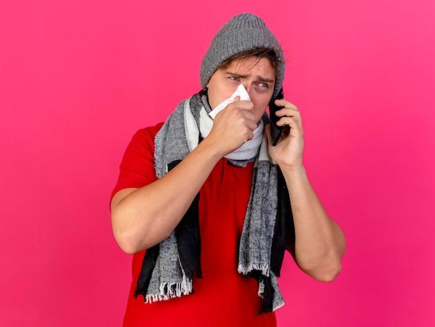 Jonge knappe blonde zieke man met winter muts en sjaal praten over telefoon neus afvegen met servet kijken kant geïsoleerd op roze muur met kopie ruimte