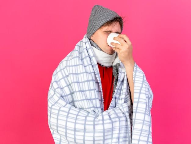 Jonge knappe blonde zieke man met winter muts en sjaal verpakt in geruite kopje thee drinken met gesloten ogen geïsoleerd op crimson achtergrond met kopie ruimte