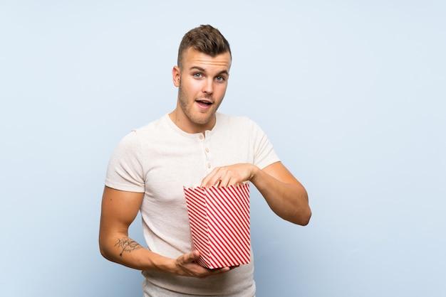 Jonge knappe blondeman die over blauwe muur popcorns eet