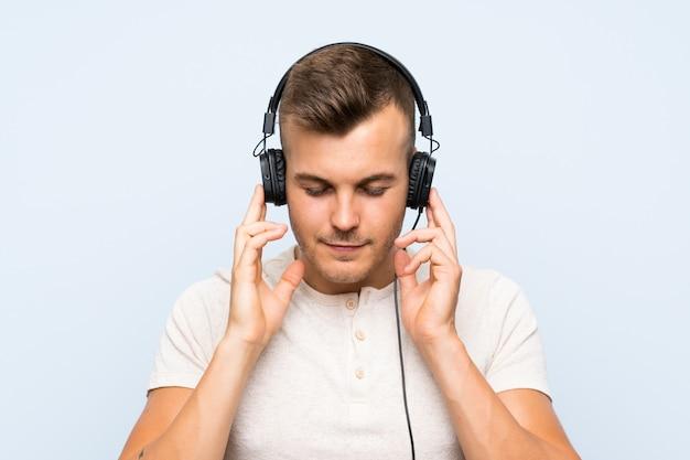 Jonge knappe blondeman over blauwe muur luisteren naar muziek met een koptelefoon