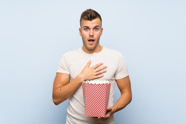 Jonge knappe blondeman over geïsoleerde blauwe muur met een kom popcorns