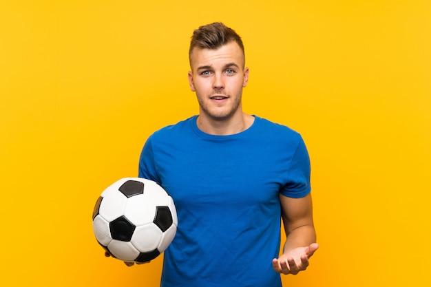 Jonge knappe blondemens die een voetbalbal over geïsoleerde geel met geschokte gelaatsuitdrukking houden