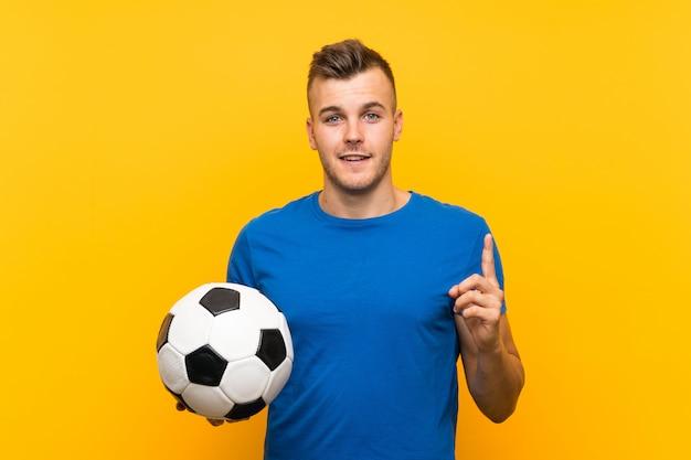 Jonge knappe blondemens die een voetbalbal over geïsoleerde gele achtergrond houden die de oplossing van plan zijn te realiseren terwijl het opheffen van een vinger