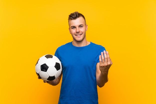 Jonge knappe blondemens die een voetbalbal over geïsoleerde gele muur houden die met hand uitnodigen te komen. blij dat je bent gekomen