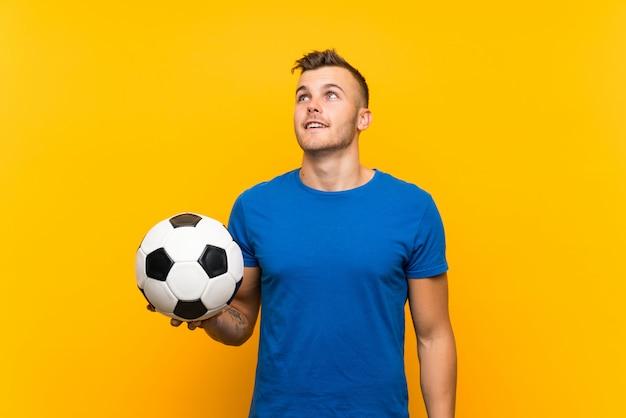 Jonge knappe blondemens die een voetbalbal over geïsoleerde gele muur houden omhoog kijkend terwijl het glimlachen