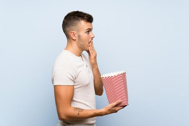 Jonge knappe blondemens over geïsoleerd blauw die een kom popcorns houden