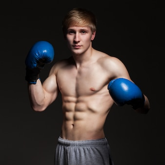 Jonge knappe bokser in blauwe handschoenen