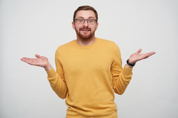 Jonge knappe brunette bebaarde man schouderophalend met opgeheven handpalmen en licht glimlachend, mosterd trui en polshorloge dragen