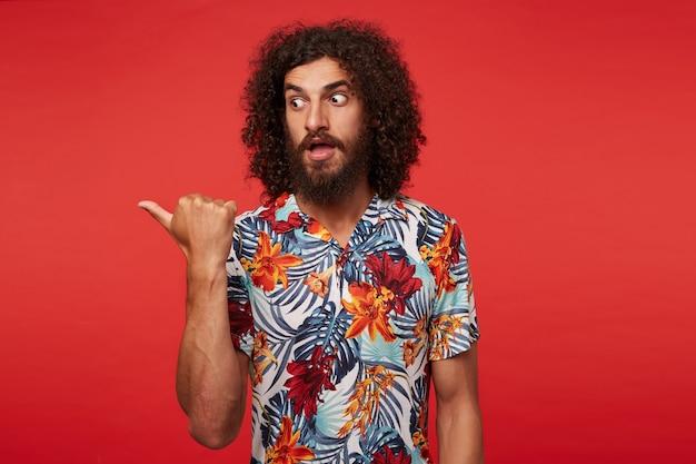 Jonge knappe brunette gekrulde man met baard bang opzij kijken met grote ogen geopend, opzij wijzend met de duim tijdens het poseren