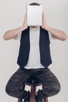 Jonge knappe brunette man met baard in wit overhemd en zwart vest met tablet voor zijn gezicht op grijze achtergrond