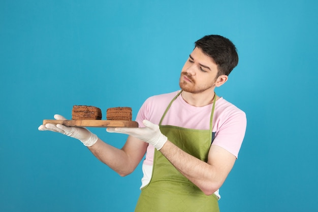 Jonge knappe chef-kok met plakjes chocoladetaart op een blauw.