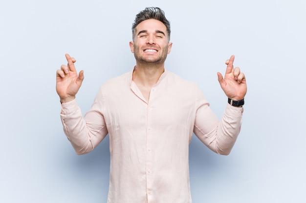 Jonge knappe coole man kruising vingers voor het hebben van geluk