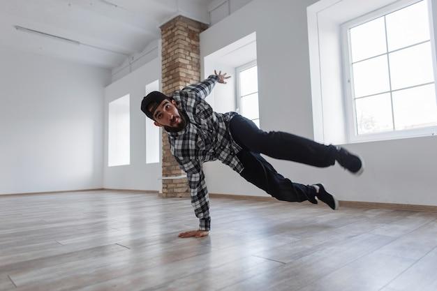 Jonge knappe danseres met een pet in beweging is dansen