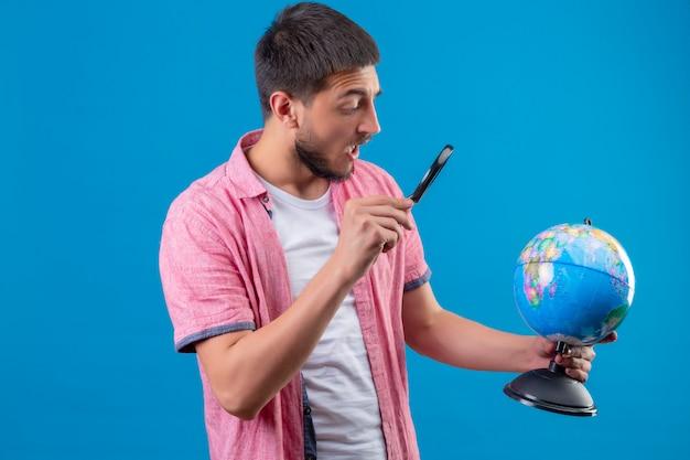 Jonge knappe de holdingsbol van de reizigerskerel en het bekijken het gebruikend vergrootglas die verrast status over blauwe achtergrond kijken