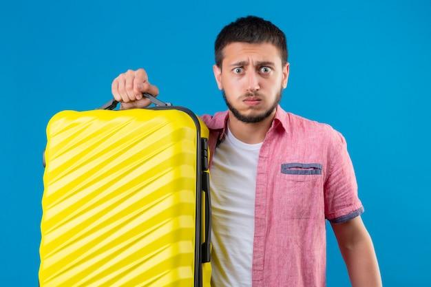 Jonge knappe de holdingskoffer die van de reizigerskerel geërgerd en gehinderde blazende wangen kijken die zich over blauwe achtergrond bevinden