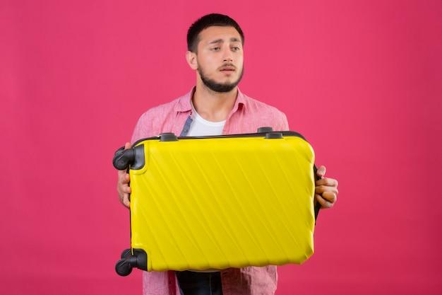 Jonge knappe de holdingskoffer die van de reizigerskerel opzij met droevige uitdrukking op gezicht kijken die zich over roze achtergrond bevinden