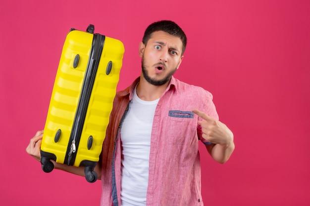Jonge knappe de holdingskoffer die van de reizigerskerel verbaasd en verrast kijken richtend aan zich status over roze achtergrond
