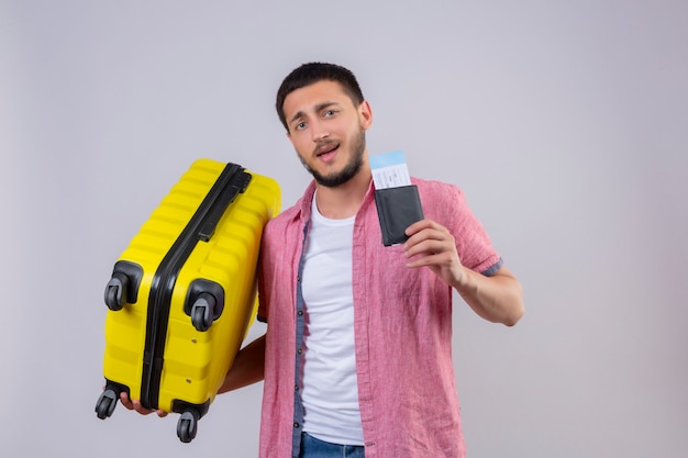Jonge knappe de holdingskoffer en luchtkaartjes die van de reizigerskerel camera met zekere glimlach op gezicht gelukkige en positieve status over witte achtergrond bekijken