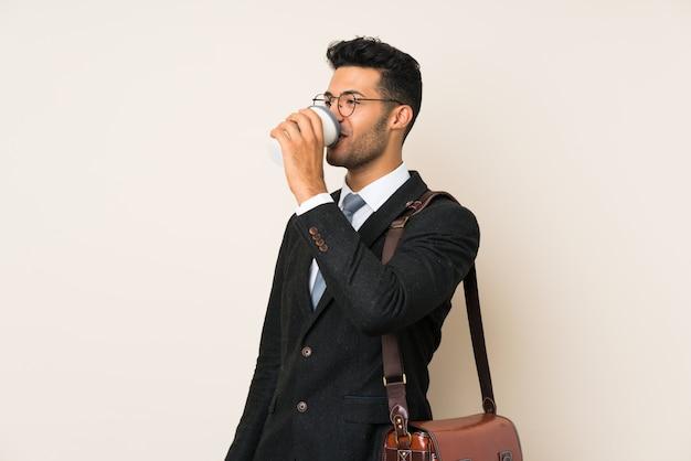 Jonge knappe de holdingskoffie van de zakenmanmens om over geïsoleerde achtergrond weg te halen