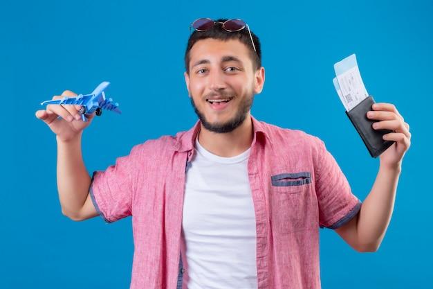 Jonge knappe de holdingsstuk speelgoed van de reizigerskerel vliegtuig en luchtkaartjes die camera bekijken die vrolijk met gelukkig gezicht glimlachen die zich over blauwe achtergrond bevinden
