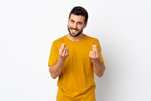 Jonge knappe die mens met baard op witte muur wordt geïsoleerd die geldgebaar maken