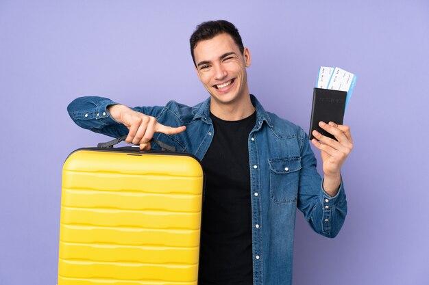 Jonge knappe die mens op purpere muur in vakantie met koffer en paspoort wordt geïsoleerd en verrast