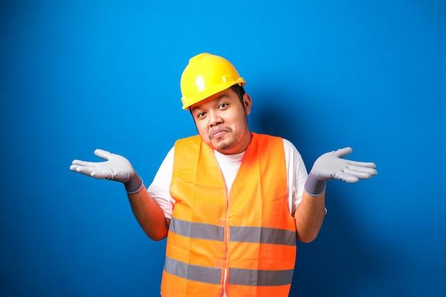 Jonge knappe dikke aziatische arbeidersman met een oranje veiligheidsvest uniform en helm geen idee en verwarde uitdrukking met opgeheven armen en handen. twijfel concept.
