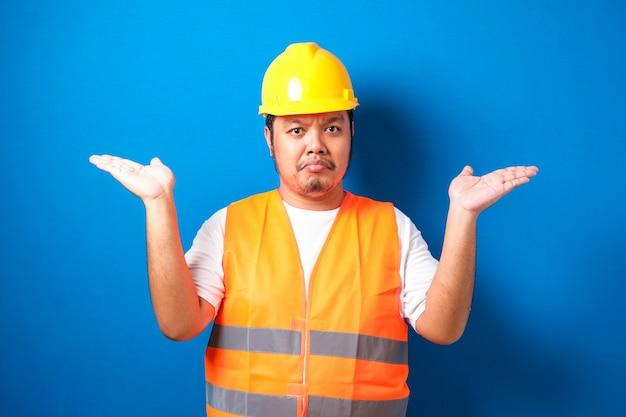 Jonge knappe dikke aziatische arbeidersman met een oranje veiligheidsvestuniform en een helm zonder idee