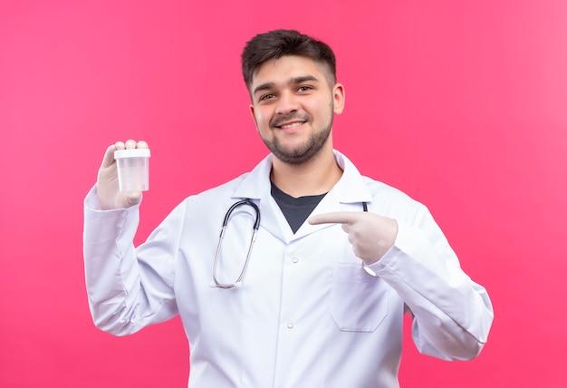 Jonge knappe dokter die witte medische jurk draagt, witte medische handschoenen en een stethoscoop, blij met resultaten die wijzen op transparante analysecontainer die zich over roze muur bevindt