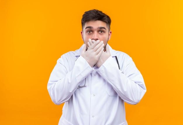 Jonge knappe dokter, gekleed in witte medische jurk, witte medische handschoenen en een stethoscoop bang zijn muis te sluiten met handen die zich over oranje muur bevinden