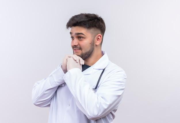 Jonge knappe dokter, gekleed in witte medische jurk witte medische handschoenen en een stethoscoop kijken naast gefascineerd staande over witte muur