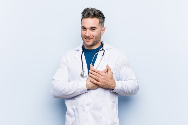 Jonge knappe dokter man heeft vriendelijke uitdrukking, palm op borst drukken. liefde concept.