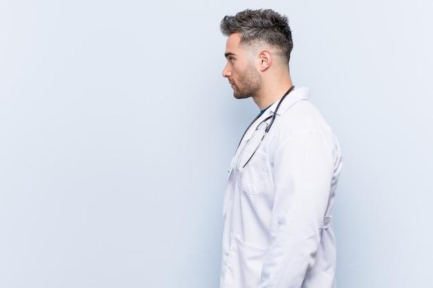 Jonge knappe dokter man staren naar links, zijwaarts poseren.