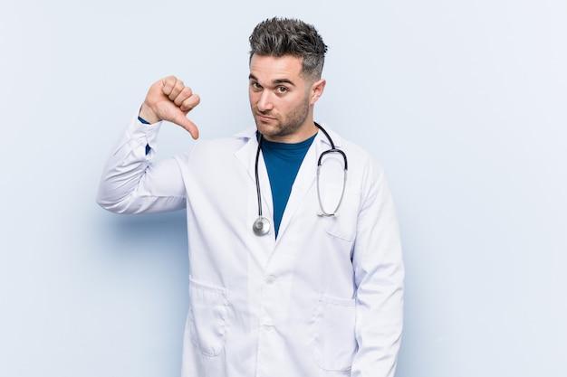 Jonge knappe dokter man toont een afkeer gebaar, duimen naar beneden