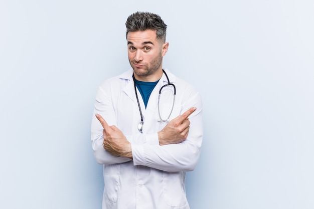 Jonge knappe dokter man wijst zijwaarts, probeert te kiezen tussen twee opties