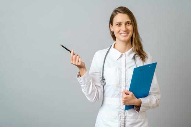 Jonge knappe dokter vrouw dragen stethoscoop glimlachend vrolijk, presenteren en wijzen