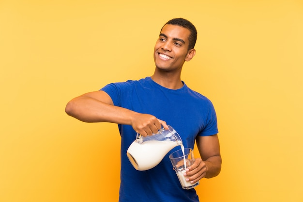 Jonge knappe donkerbruine mens over gele muur die ontbijtmelk heeft