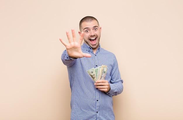 Jonge knappe en mens die vriendelijk glimlachen kijken, nummer vijf of vijfde met vooruit hand tonen, die met dollarbankbiljetten aftellen