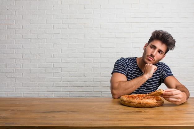 Jonge knappe en natuurlijke man zittend op een tafel denken en opzoeken, verward over een idee