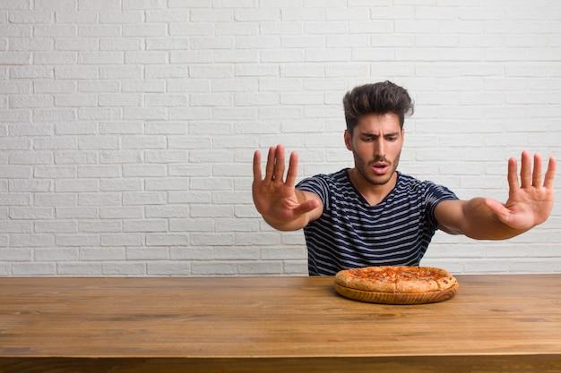 Jonge knappe en natuurlijke man zittend op een tafel serieus en vastberaden, hand in de voorkant