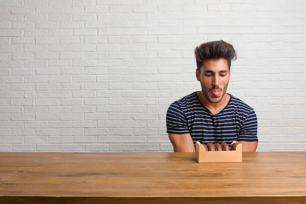 Jonge knappe en natuurlijke man zittend op een tafel uitdrukking van vertrouwen en emotie, leuk en vriendelijk, met tong als een teken van spel of plezier. chocolade donuts eten.
