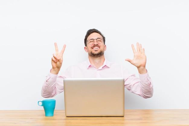 Jonge knappe en zakenman die vriendelijk glimlachen kijken, nummer zeven of zevende met vooruit hand tonen, die aftelt