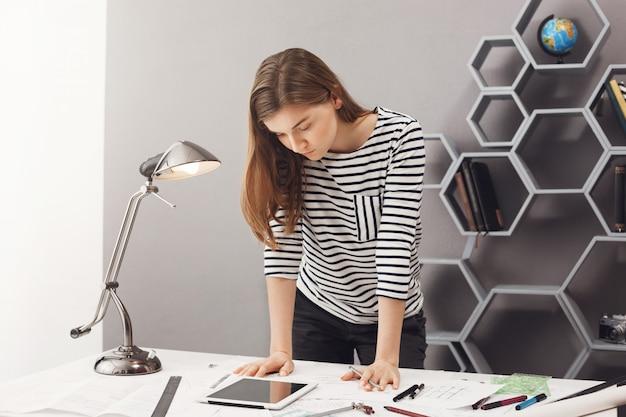 Jonge knappe ernstige vrouwelijke ontwerperstudent met donker haar in modieuze toevallige uitrusting die zich dichtbij lijst bevinden, die in digitale tablet kijken, die sommige details proberen te achterhalen.