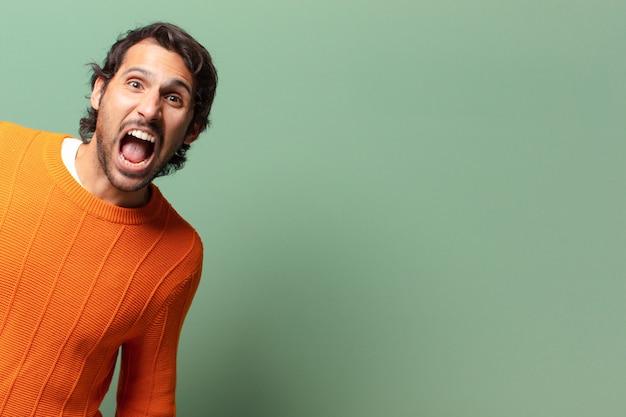 Jonge knappe expressieve en boze indiase man met een kopie ruimte