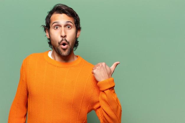 Jonge knappe expressieve en verraste indiase man met een kopieerruimte
